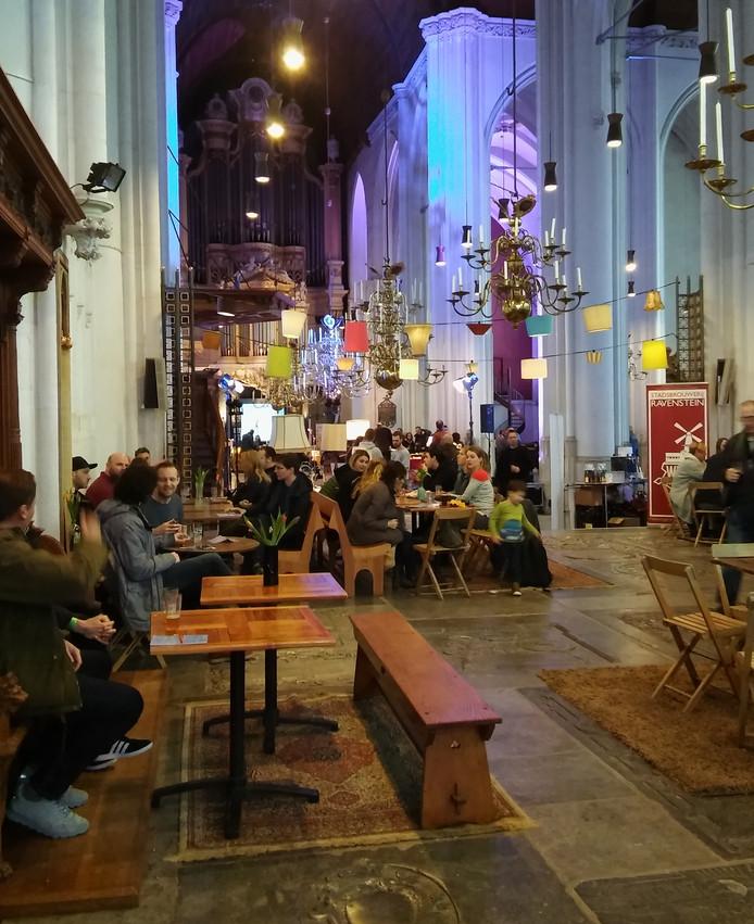 Bezoekers genieten in de Nijmeegse Stevenskerk van een van de veertig bieren die wordt geschonken.