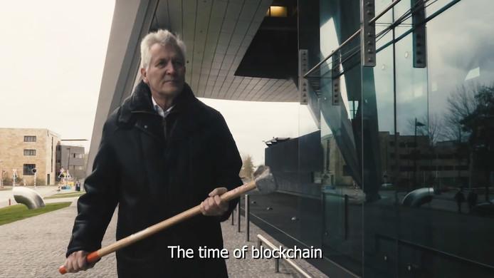Dirk Scheringa met een grote hamer op de Zuidas
