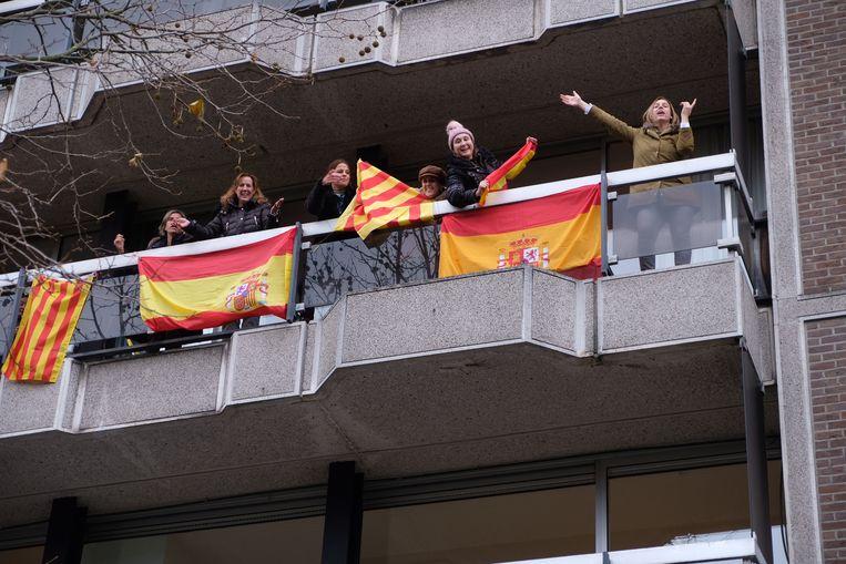 Een klein tegenprotest: enkele vrouwen hebben Spaanse vlaggen opgehangen aan een balkon langs het parcours.
