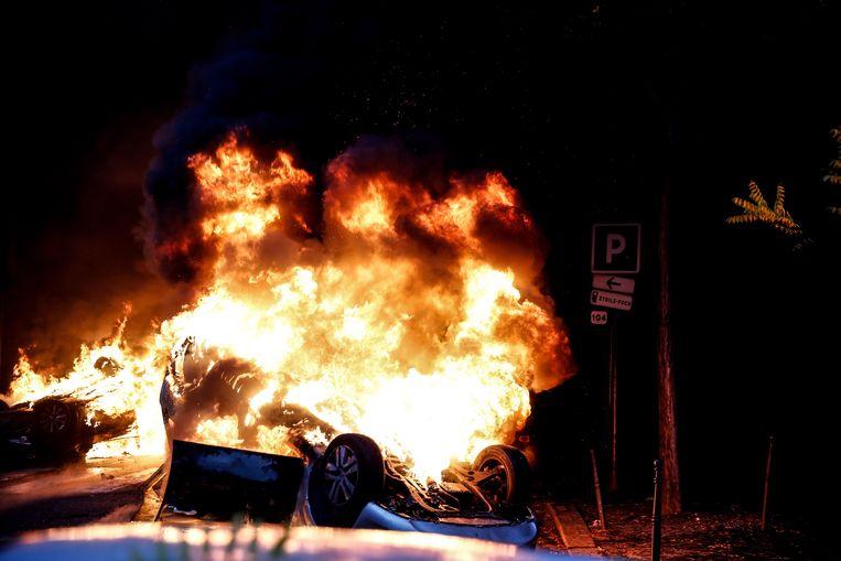 Een auto brandt uit vlak bij de plek waar zaterdag in Parijs werd gedemonstreerd. Beeld AFP
