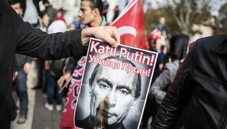 Een demonstrant steekt een foto van Poetin, met erboven de tekst 'Poetin, moordenaar!' in brand bij een anti-Ruslanddemonstratie in Istanboel Beeld afp