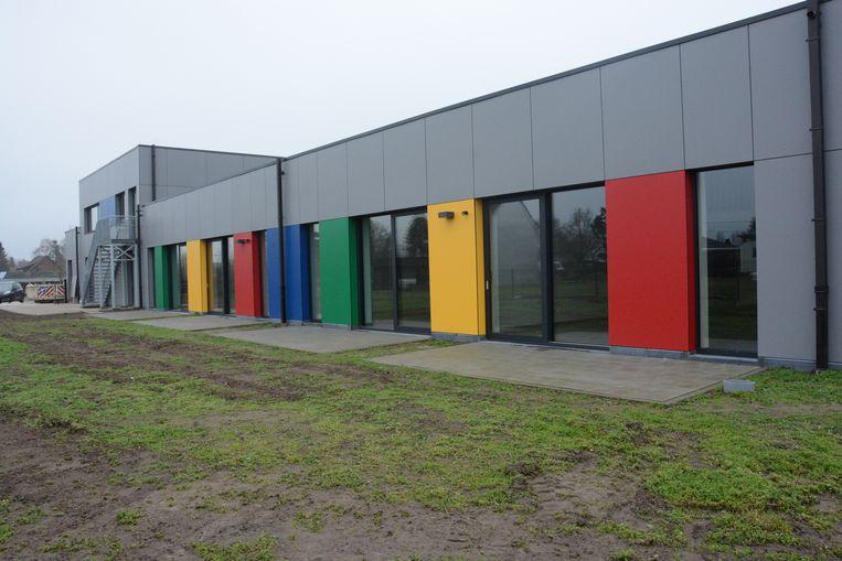 Alle klassen hebben schuiframen tot op de grond die uitkijken op de groene buitenspeelruimte.