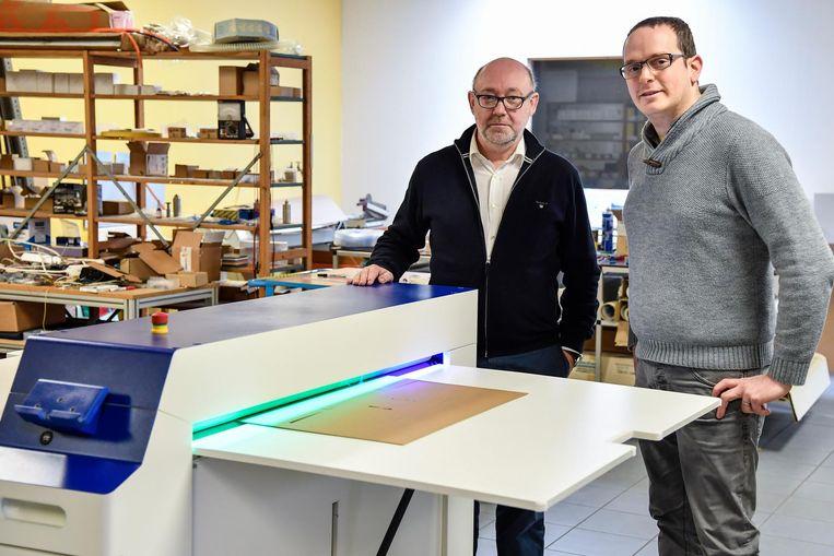 Kristof Roose (rechts) bij de Slimbox, een machine die karton snijdt en waardoor dozen op maat gemaakt kunnen worden.