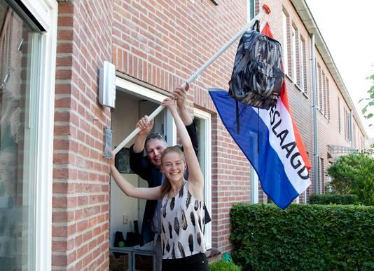 Docent Johan van der Leeden helpt Kirsten Danz met de vlag ophangen. Zij behaalde een tien voor het MAVO eindexamen economie