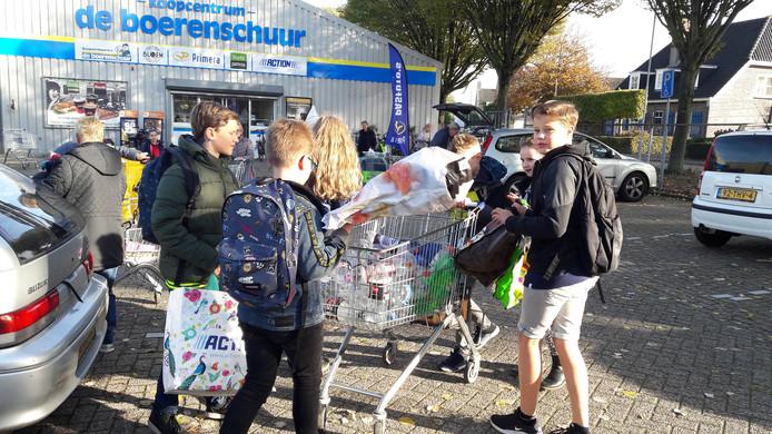 Joep (helemaal rechts achter het winkelwagentje) levert met zijn klasgenootjes lege flessen in.