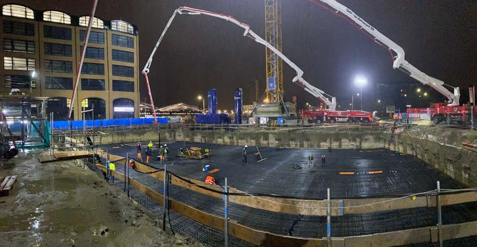 Werken in het ochtendduister: het storten van beton voor de kelder van De Brabander is begonnen. Links kantoorgebouw Plan-T.