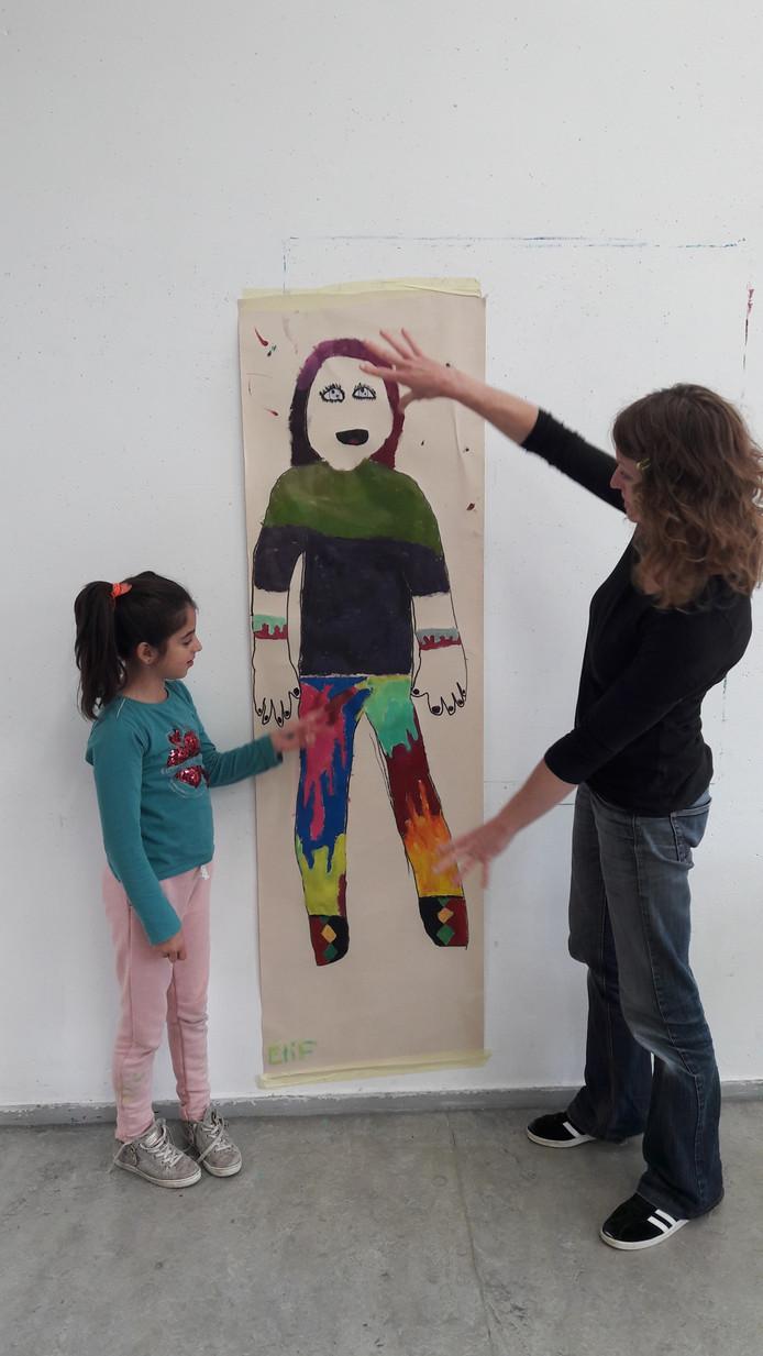 Elif hangt haar tekening op die ze in De Aleph heeft gemaakt.