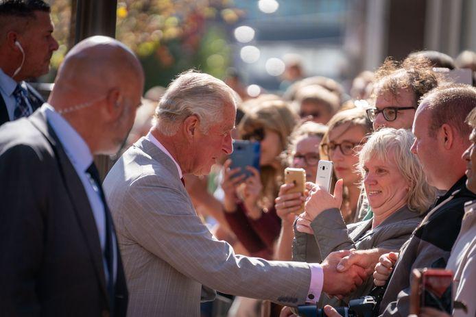 Prins Charles tussen het publiek, met alom beveiligers aan zijn zijde.