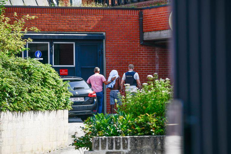 Eén van de verdachten wordt het gerechtsgebouw binnengeleid.