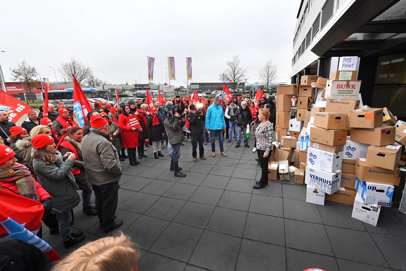 FNV Zorg & Welzijn en ruim 100 medewerkers van de Hoenderloo Groep voeren actie bij hoofdkantoor Pluryn, woordvoerder Marian Draaisma neemt de dozen in ontvangst.