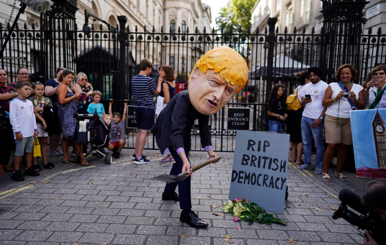 Een demonstrant doet Johnson na buiten zijn ambstwoning op Downing Street. Beeld EPA