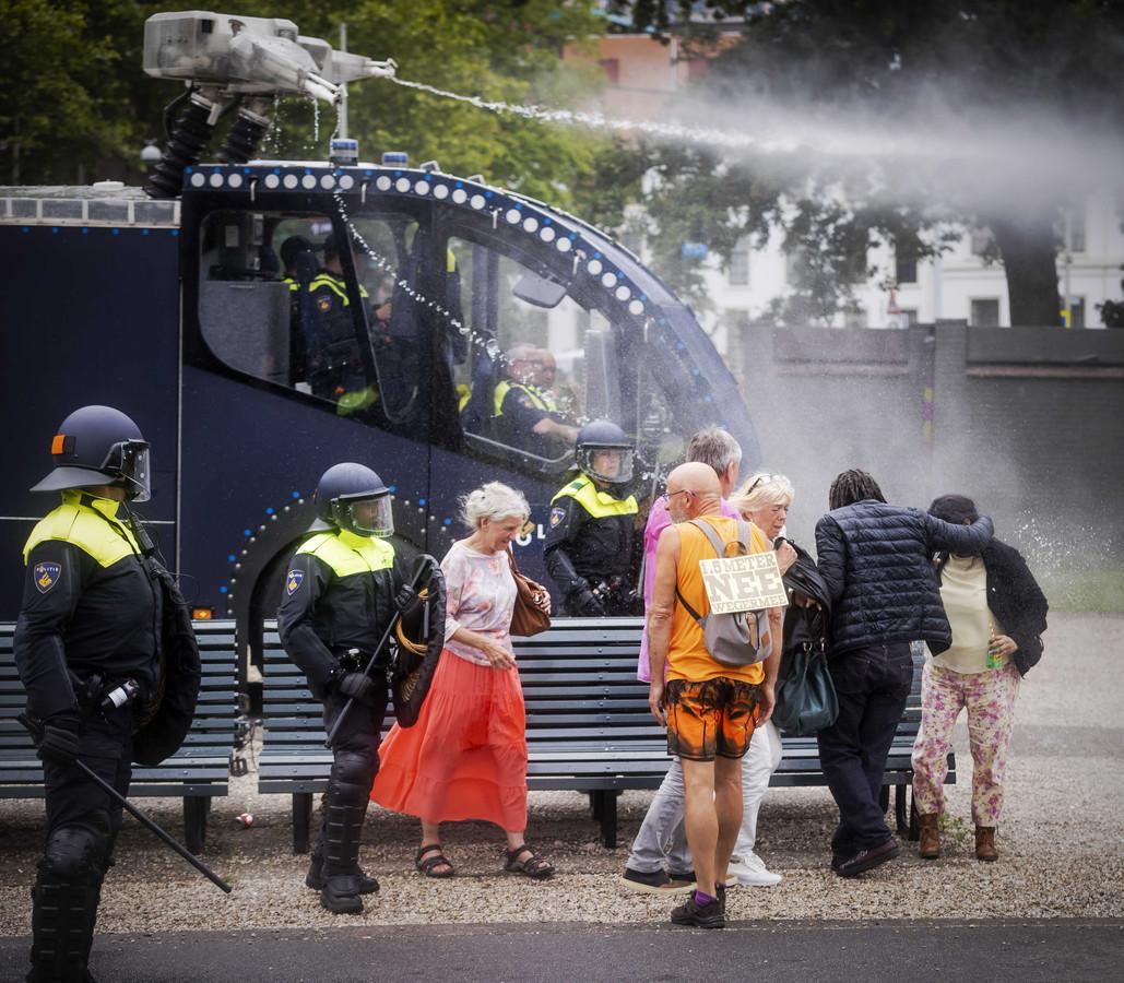 Mensen worden natgespoten door het waterkanon van de politie