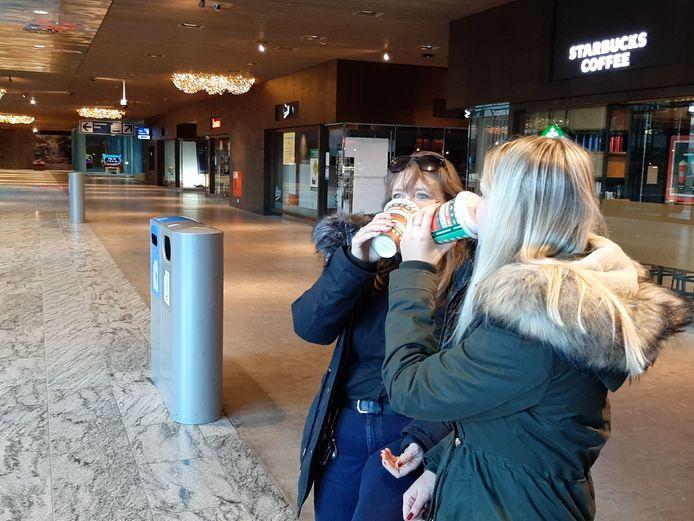 Bij gebrek aan meubilair op het station, drinken Linda (r) en Bibi (l) nu maar even staand hun koffie op.