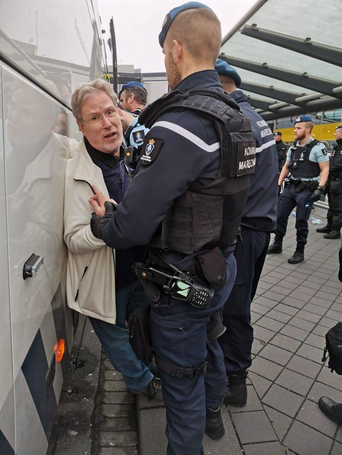 Alfred Blokhuizen wordt door de marechaussee tegen de arrestantenbus gedrukt.