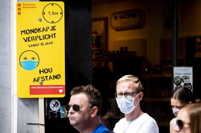Een bord met informatie over mondkapjesplicht op de Nieuwendijk in Amsterdam.