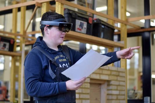 Een van de derdejaars leerlingen van VMBO basis kader kan door de hololens zijn ontwerp van de bouwplaats in het werkelijke formaat in de ruimte geprojecteerd zien.