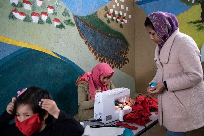 Vrouwen in kamp Moria maken beschermende mondkapjes.