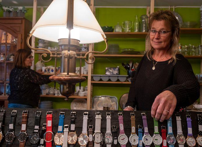 Ciska Minderhoud laat een collectie horloges 'recht van de markt' zien, terwijl Marijke Kranenburg achterin een paar kopjes rechtzet.