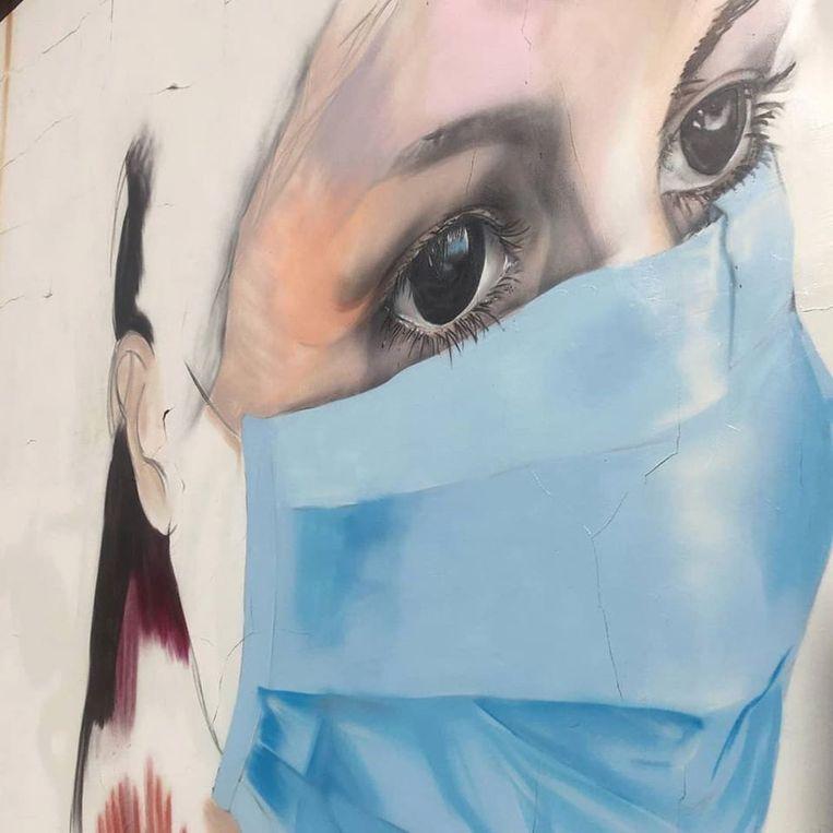 De mural op de Herentalsebaan beeldt een verpleegkundige met een mondmasker af.