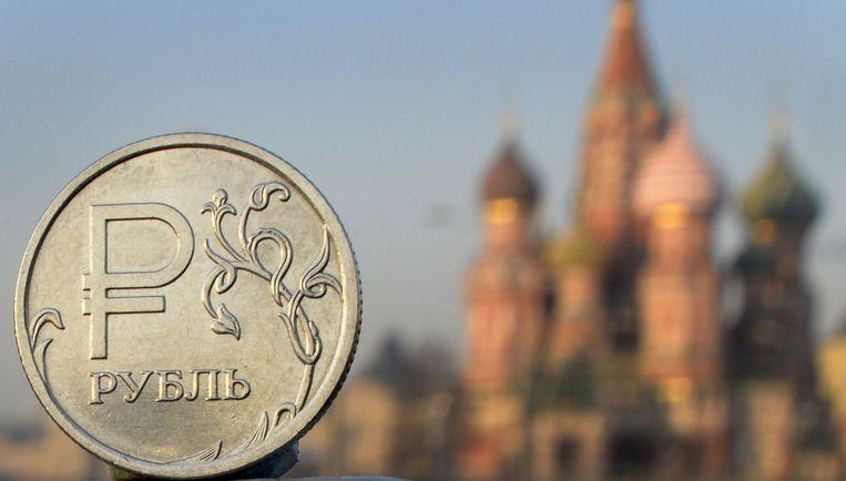 Een Roebelmunt met op de achtergrond de Pokrovkathedraal in Moskou. Beeld afp