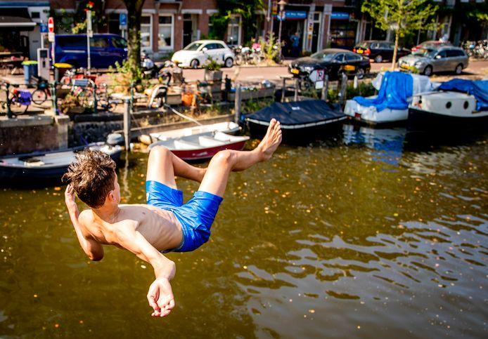 Jongens springen in de Kattensloot in Amsterdam op een bloedhete dag.