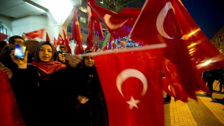 Aanhangers van Edogan zwaaien met Turkse vlaggen voor het Turkse consulaat in Rotterdam. Beeld ap