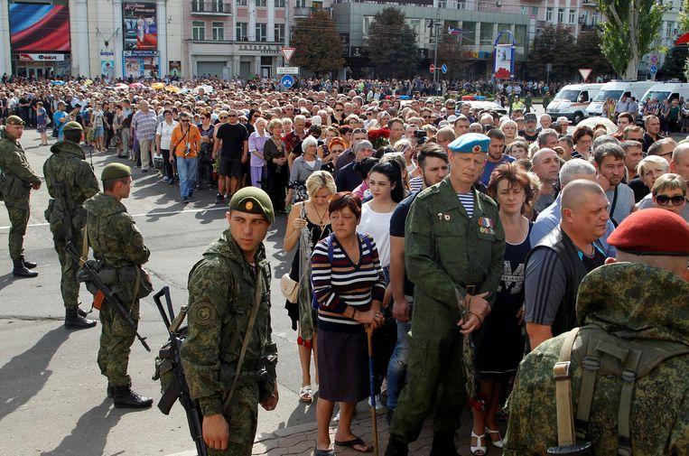 Een lange rij mensen wacht om een glimps op te vangen van de doodskist van Zachartsjenko.