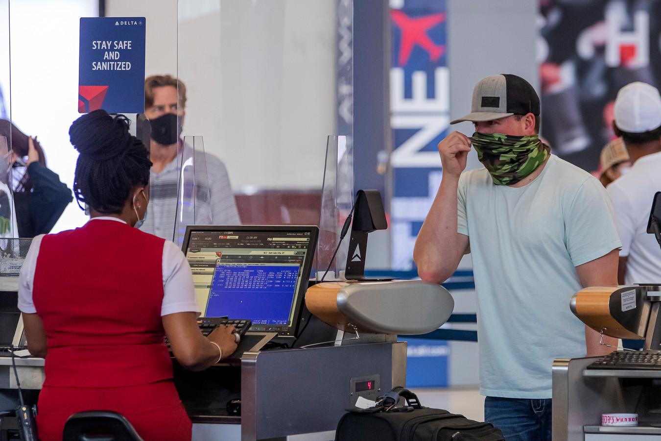 Mensen met mondkapjes en sjaals op bij een desk van Delta Airlines op een luchthaven in de VS.
