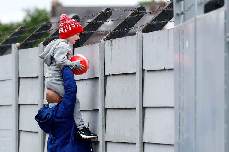Een fan bekijkt de training op Melwood, het trainingscentrum van Liverpool. Beeld REUTERS