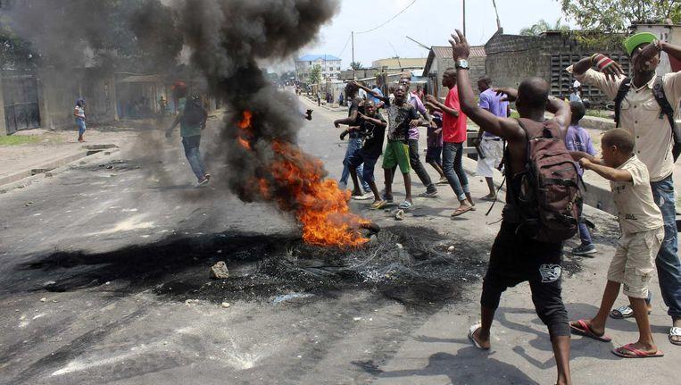 Betogers staken autobanden in brand tijdens protesten in Kinshasa gisteren.