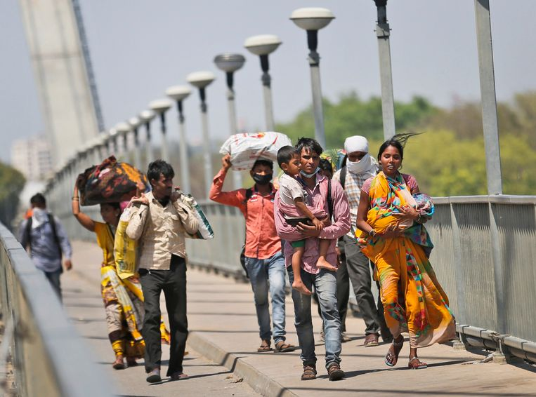 Arbeidsmigranten uit Gurugram met hun familie te voet onderweg naar hun dorp.