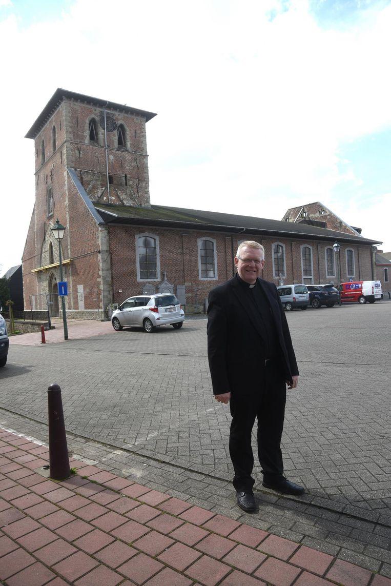 Pastoor Andy Penne met achter hem de afgebrande kerk.
