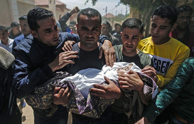 Een kind dat volgens de Palestijnse autoriteiten is overleden bij een Israëlisch bombardement op zaterdag. Beeld AFP