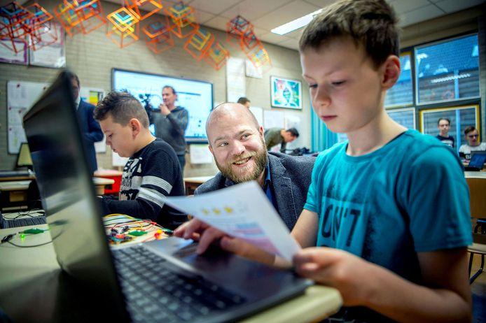 Peter Kerris (links) kijkt toe, terwijl leerlingen van De Appelhof aan het programmeren zijn.