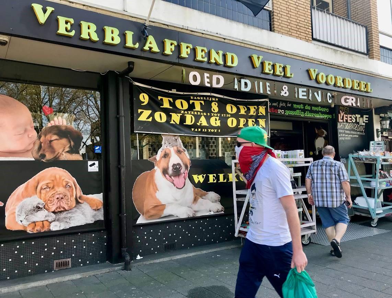 Met een mondkapje op loopt een man langs Robs Dierenshop aan de Slinge in Rotterdam-Pendrecht.