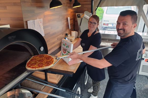 An en Bart steken een pizza in de oven van hun foodtruck 'Il Carrello'.