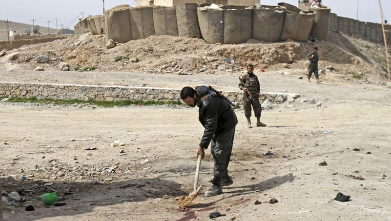 Een Afghaanse politieman bedekt bloedsporen met zand in Kandahar op de plek waar zondag een aanslag werd gepleegd. Beeld ap