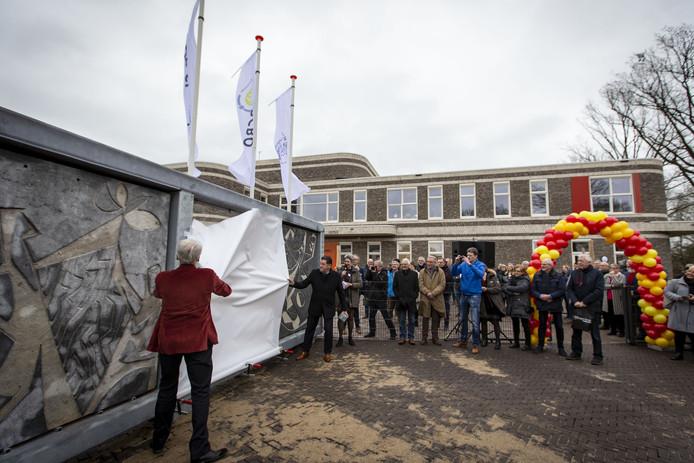De brede school Kadans wordt officieel geopend door wethouder Roel Koster en Bert Dorrestein (rood jasje) . Tegelijk wordt ook het Sgraffito kunstwerk onthuld . Om dat kunstwerk is veel te doen geweest . De verplaatsing werd fors duurder dan ingeschat.
