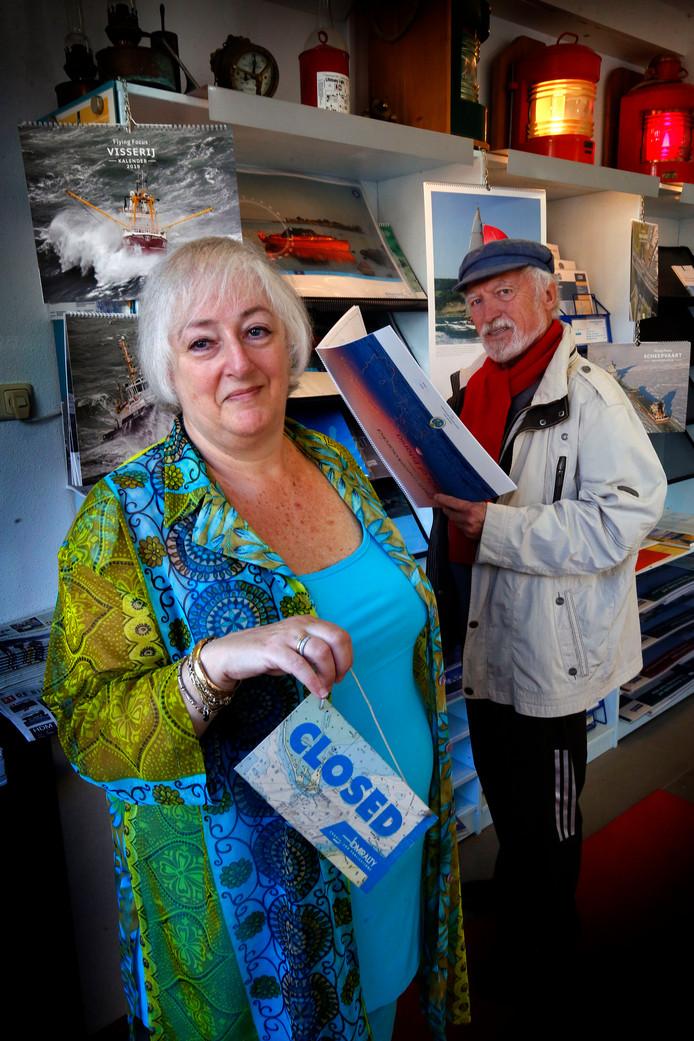 Marja Klijnkramer staat met het open-en dichtbordje in haar handen, dat binnenkort alleen nog maar gesloten zal laten zien. Buurman én fervent zeiler Tom Zijlstra bekijkt een zeekaart.