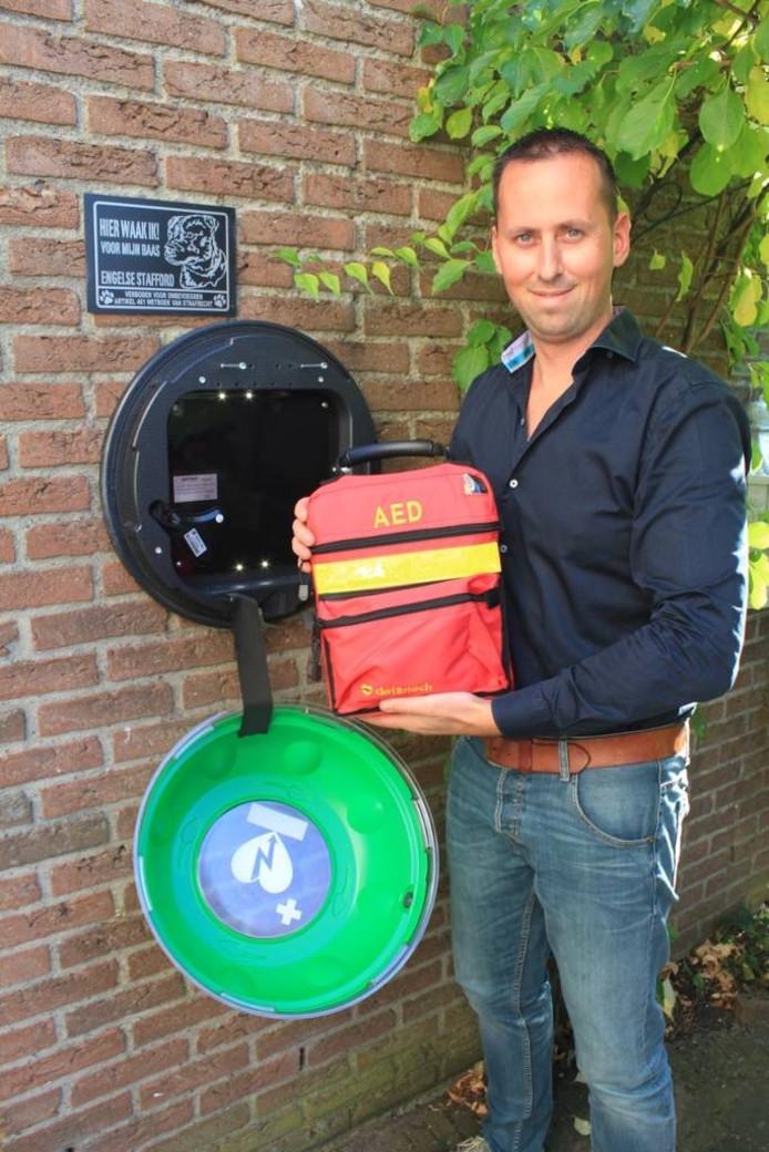 Alwin Voorhorst en de AED aan de buitenmuur.