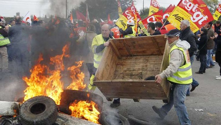 Medewerkers van een Franse olieraffinaderij maken een blokkade. Beeld reuters