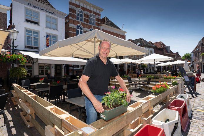 Peter Klerkx  uitbater van het Wapen van Heusden zet de bloembakken op zijn plek op het aangepaste coronaterras.