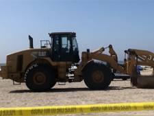 Une femme allongée sur la plage écrasée par un engin de chantier
