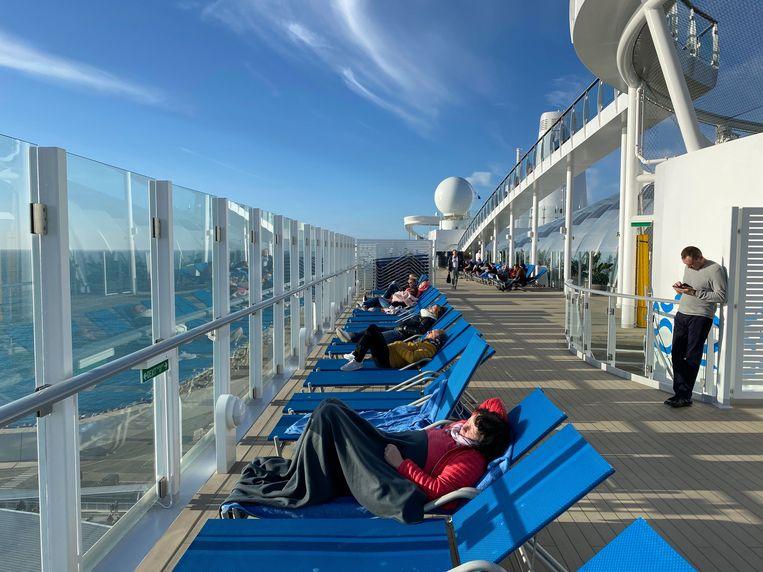 Er heerst geen paniek op het cruiseschip: passagiers proberen al zonnend de tijd te doden.