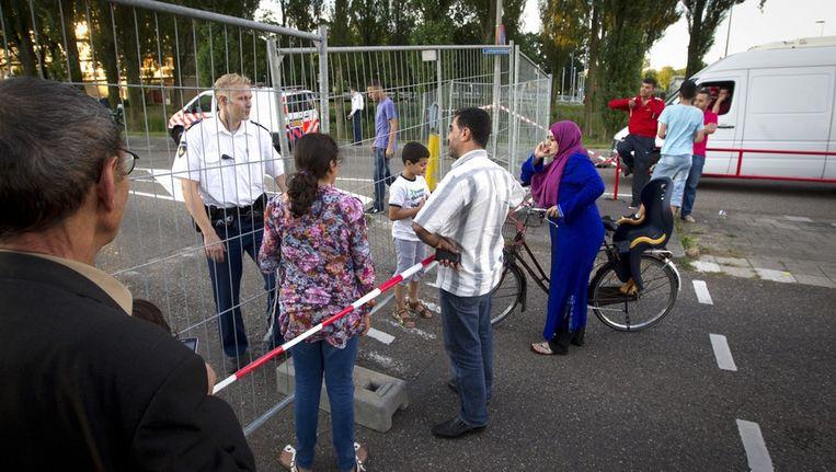 Bewoners kunnen hun wijk Kanaleneiland niet in, omdat de politie de wijk heeft afgesloten vanwege vrijgekomen asbest in twee woningen aan de Stanleylaan. Beeld anp