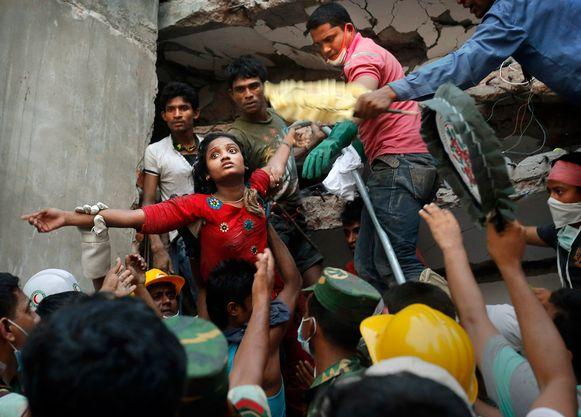 Een vrouw wordt uit het puin van de ingestorte textielfabriek gehaald.