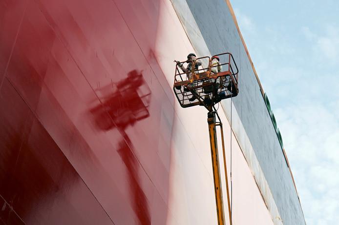 Op een zogenoemd droog dok in Dubai wordt een boot geverfd.