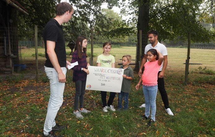 Daan Overtoom (links) neemt  namens de kinderboerderij de cheuqe in ontvangst die Stella, Lore, Mischa en Shirley (vlnr) van Het Kootertje aanbieden. Achter hen staat Frenkie Vermeulen van de bso.