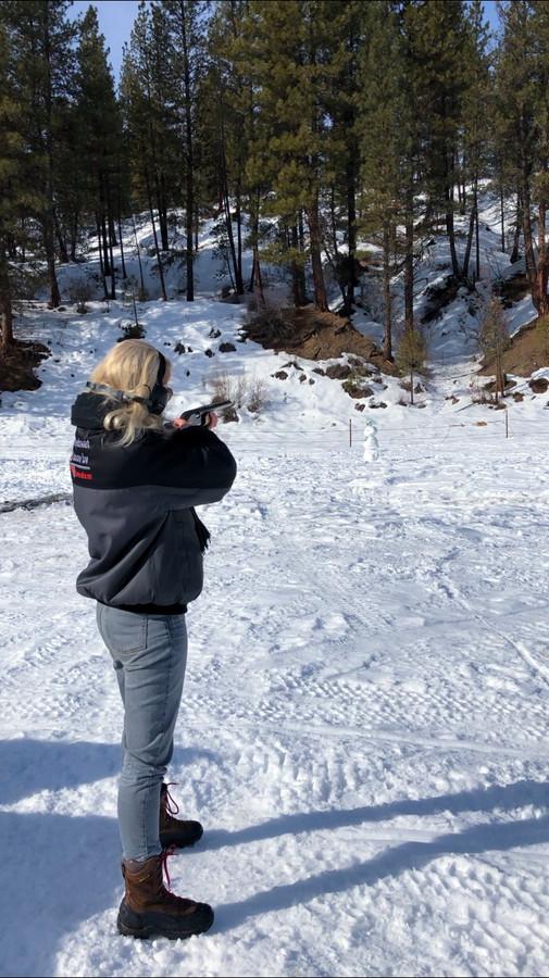 Marieke schiet met een geweer op een sneeuwpop.
