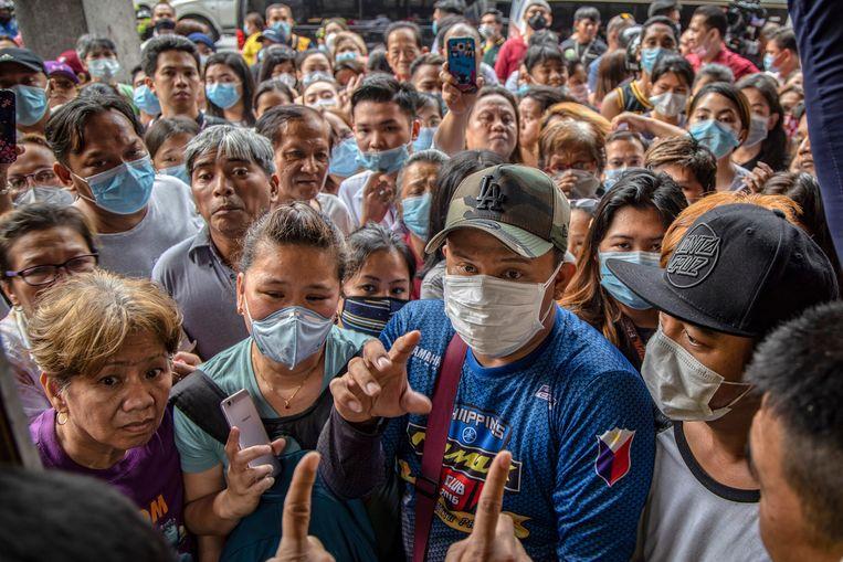 In de Filipijnse hoofdstad Manilla groeperen mensen bijeen in de hoop gezichtsmaskers te kunnen kopen.  Beeld Getty Images